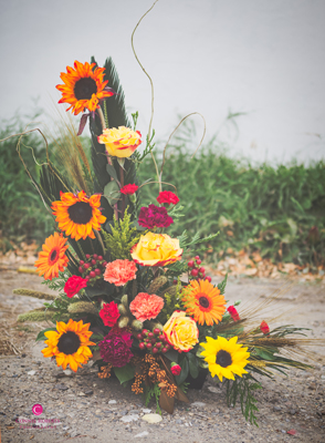 Sunflowers, orange roses, wheat and carnations bring this thanksgiving arrangement to life