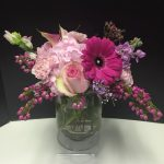 Pink flowers in this arrangement include roses, gerbera daisies and carnations
