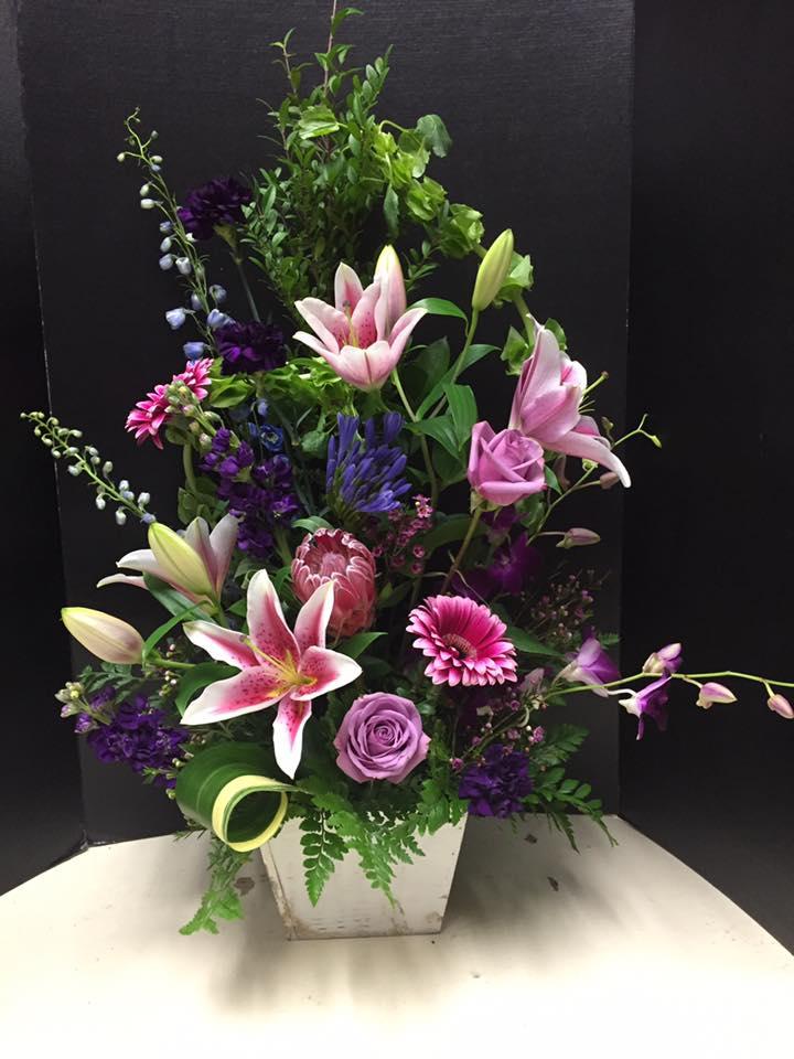 Stargazer Lilies, purple roses, pink gerbera daisies overflow in this beautiful large floral arrangement by Casa de Flores