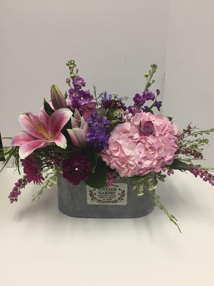 Hydrangea, stargazer lilies in a vintage garden tin container